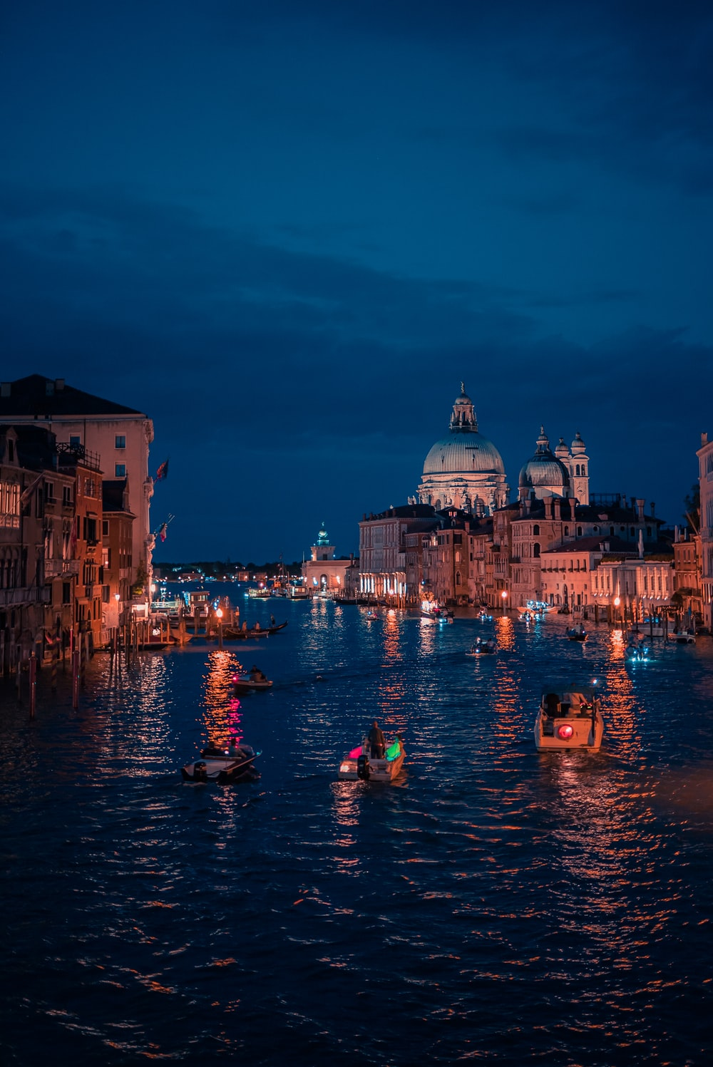 people riding on boat on river near buildings during night time