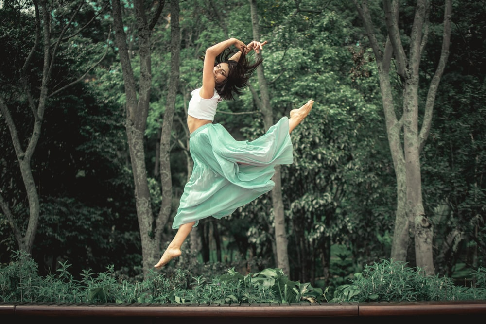 woman in white dress jumping on brown wooden fence during daytime
