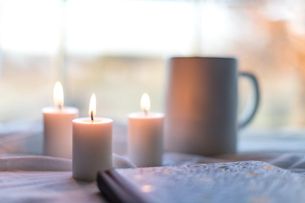 white pillar candles on white table