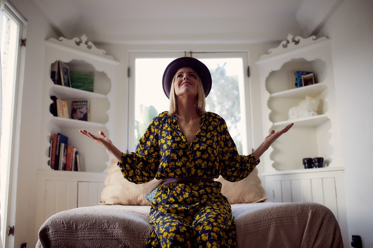 Mulher sorrindo sentada em uma cama olhando para cima e com as duas palmas da mão em direção ao céu veste uma roupa florida azul e amarelo com chapéu. Sinalizando a gratidão, uma prática comum no final de uma meditação.