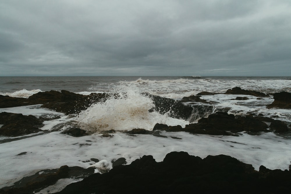 ocean waves crashing on rocks under white clouds during daytime