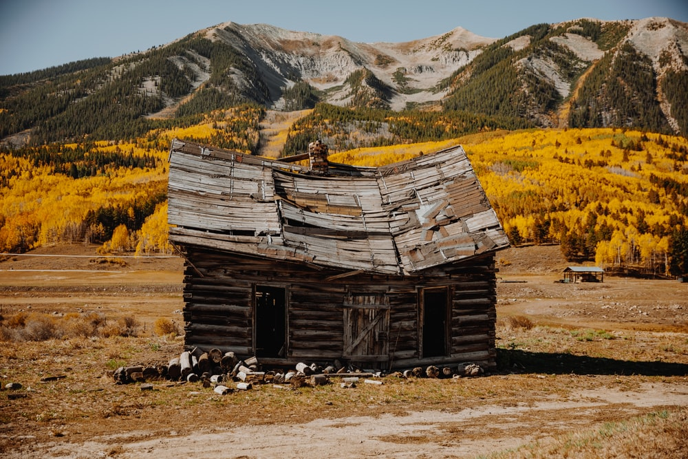 brown wooden house on brown grass field near mountain during daytime