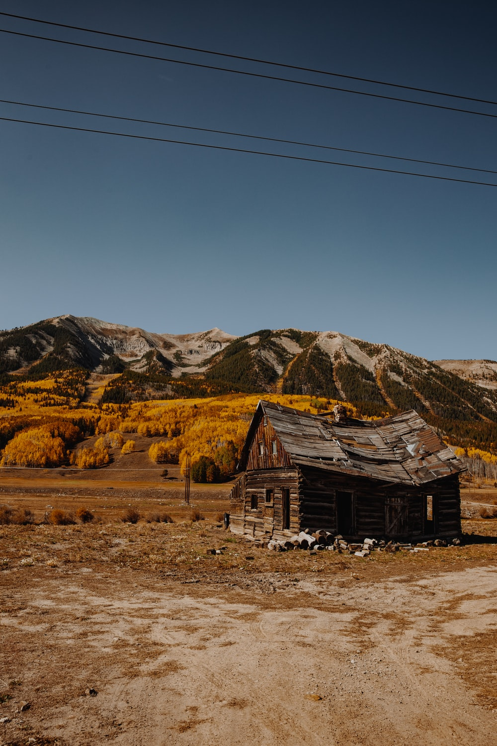 brown wooden house on brown field near brown mountains under blue sky during daytime