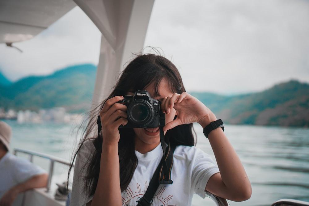 woman in white shirt holding black dslr camera