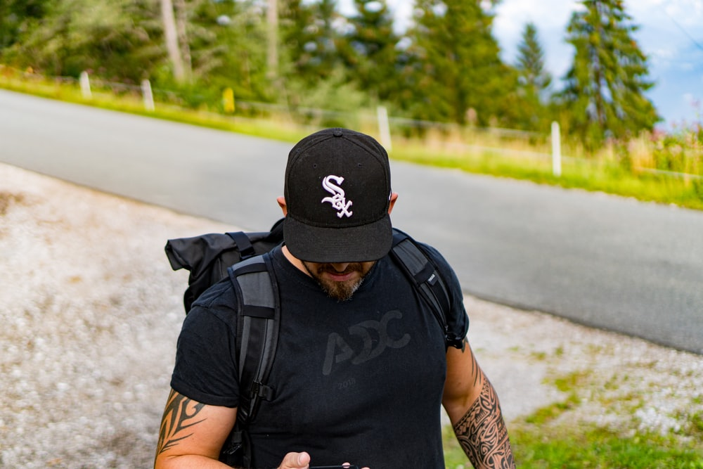 man in black nike backpack and black backpack standing on road during daytime