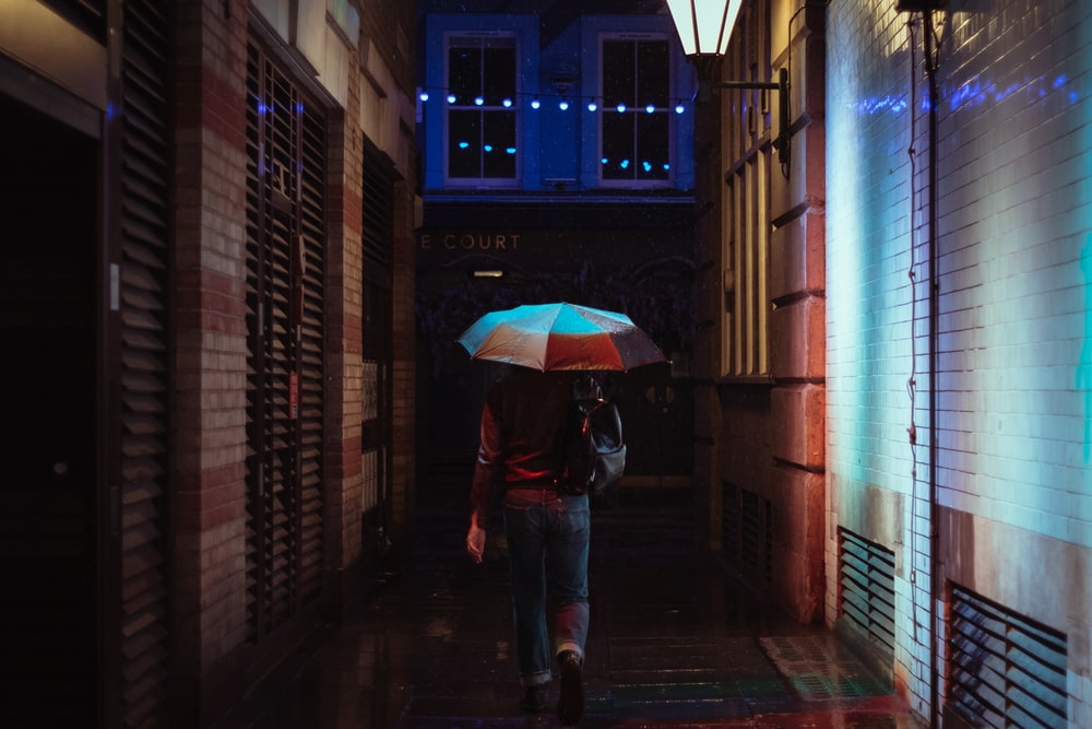person in black jacket and blue denim jeans holding umbrella walking on sidewalk during daytime
