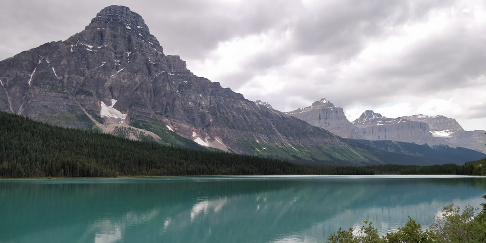 green lake near mountain under cloudy sky during daytime