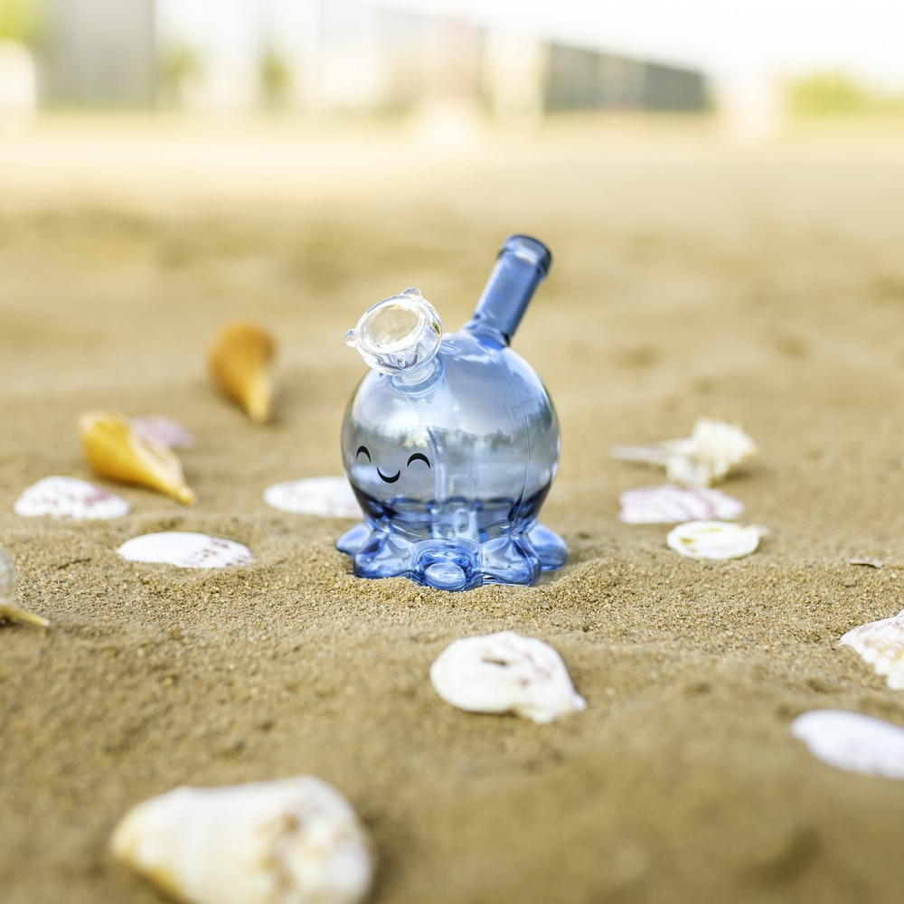 blue glass bottle on brown sand