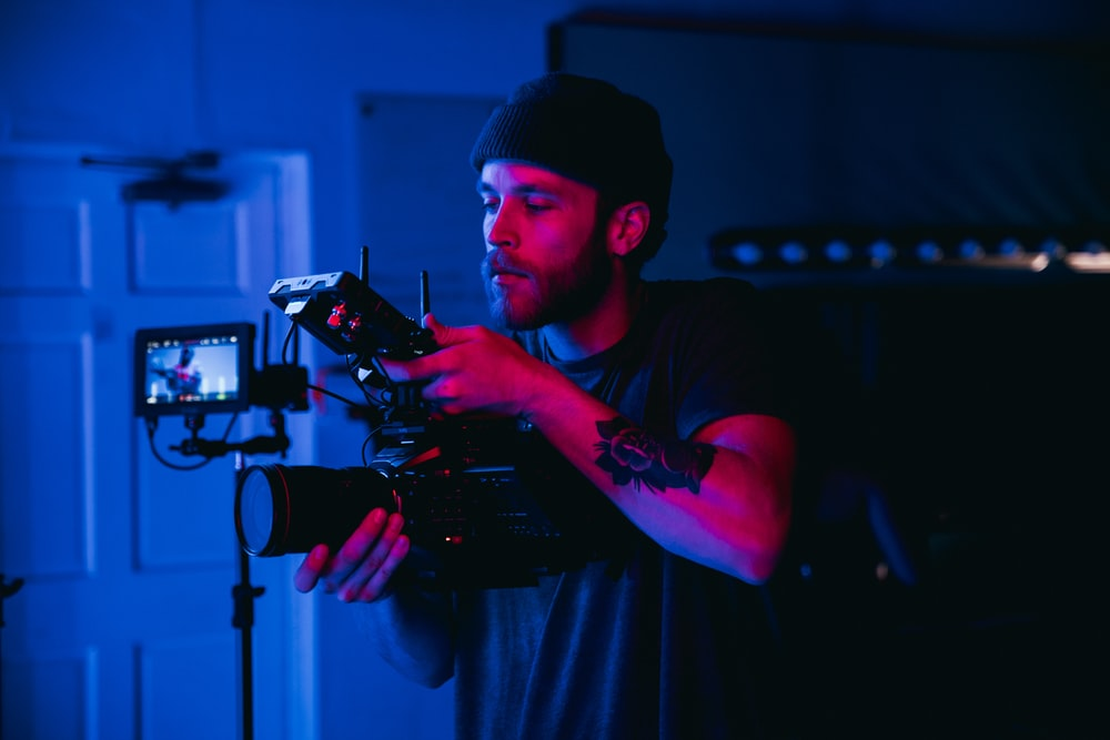 man in black t-shirt holding video camera