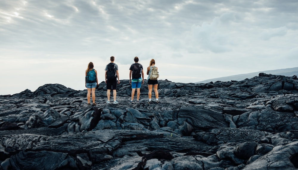 group of people standing on rocky hill under cloudy sky during daytime