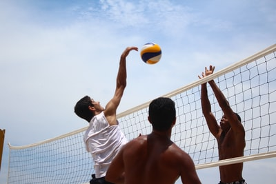 man in white shorts playing volleyball during daytime volleyball zoom background