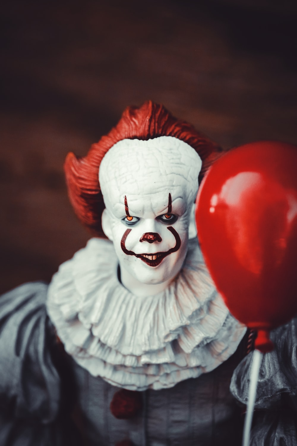 white and red clown holding heart balloon
