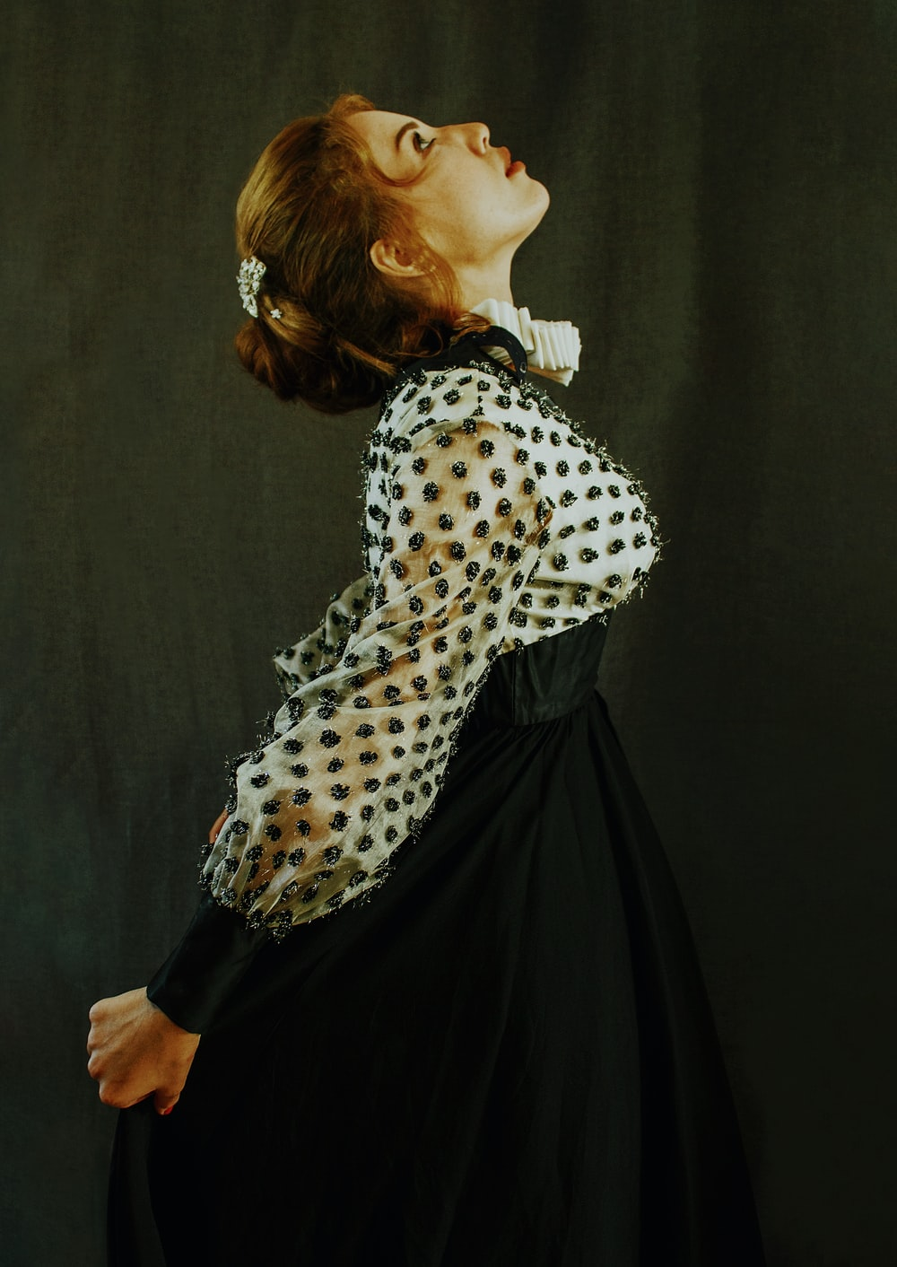 woman in white and black polka dot long sleeve shirt and black skirt
