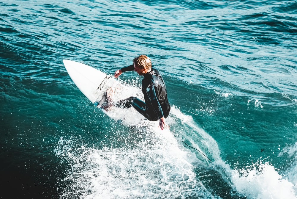 man in black wet suit riding white surfboard on sea waves during daytime
