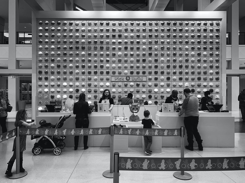 grayscale photo of people standing in front of table