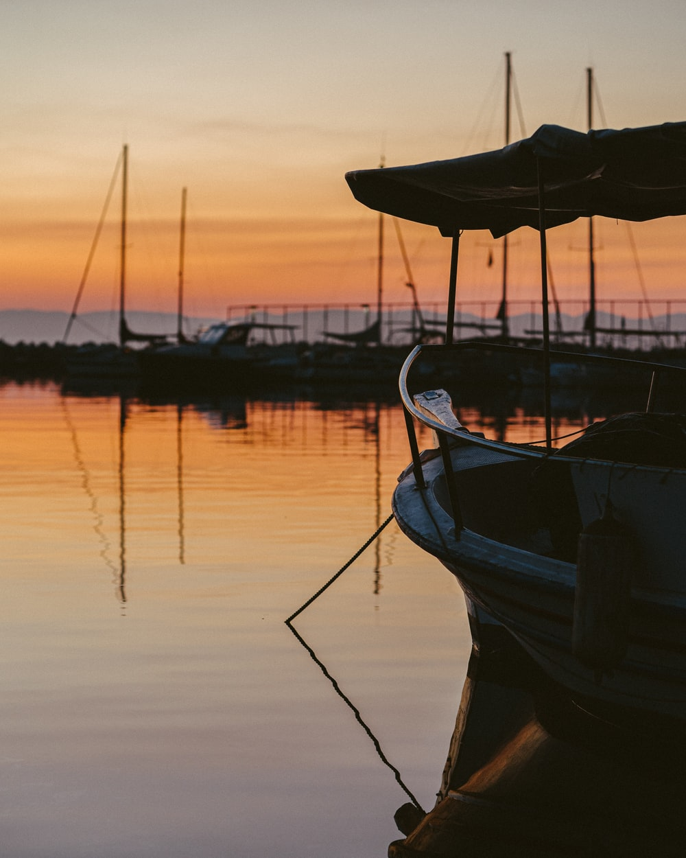 blue and brown boat on water during sunset