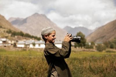 man in black coat holding black dslr camera photo zoom background