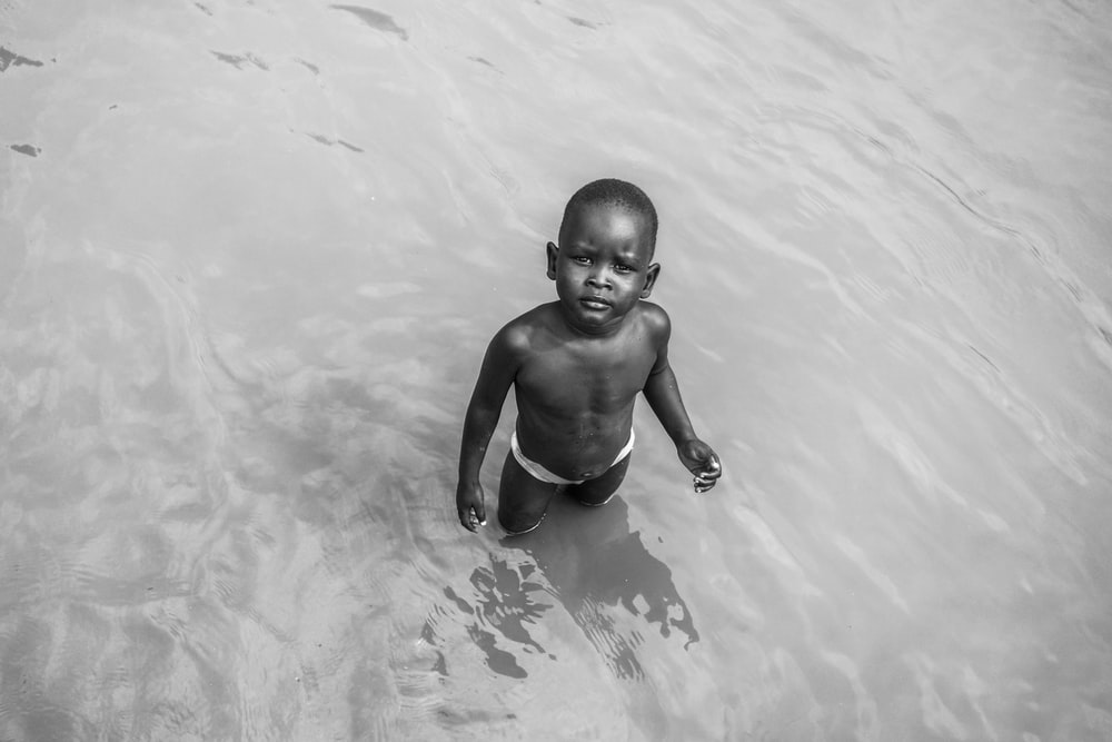grayscale photo of topless boy on water