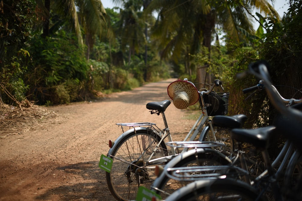 black and gray bicycle on brown dirt road during daytime