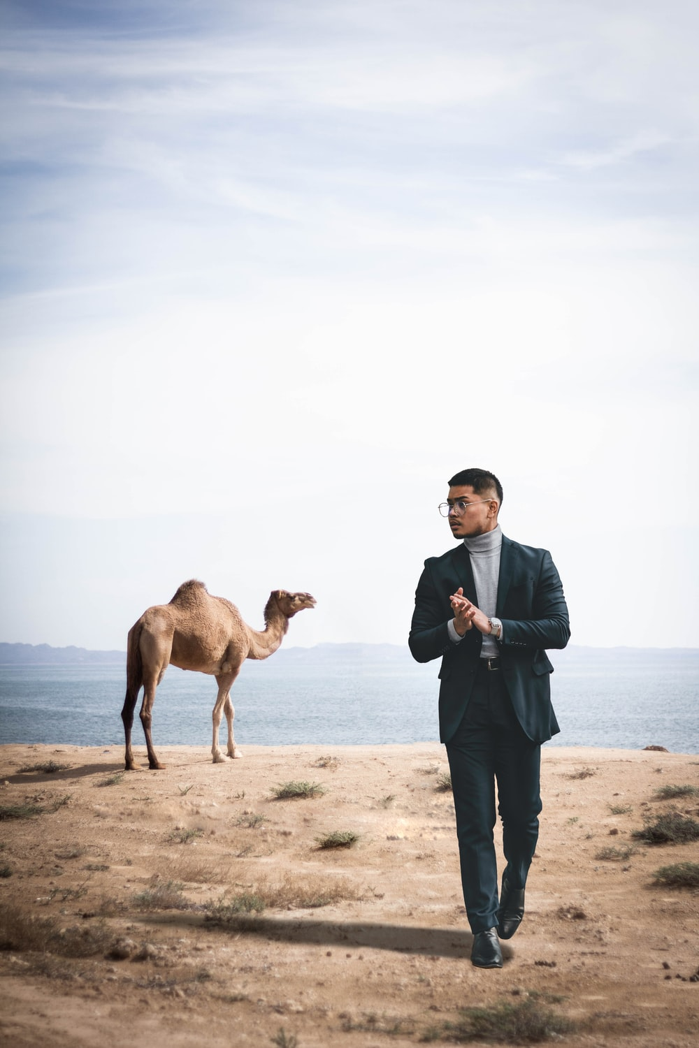 man in blue dress shirt and black pants standing beside brown camel during daytime