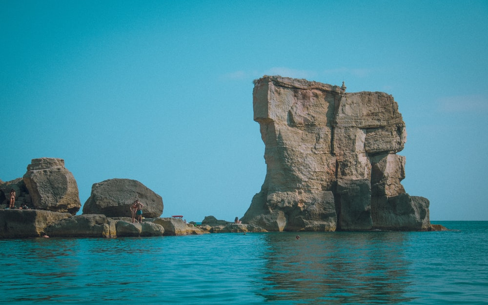 brown rock formation on blue sea under blue sky during daytime