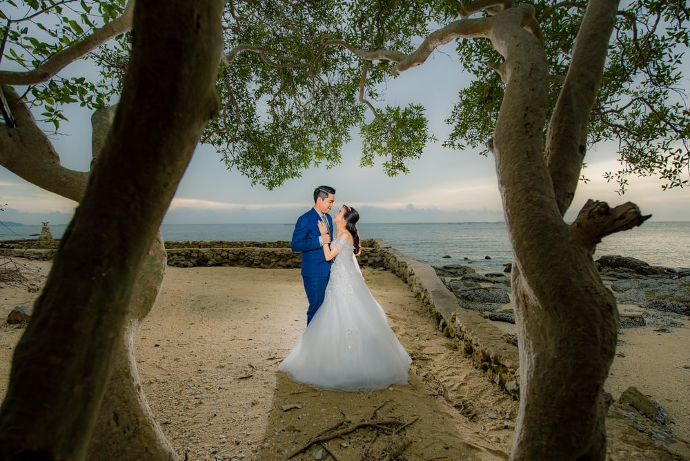 bride and groom kissing on beach during daytime