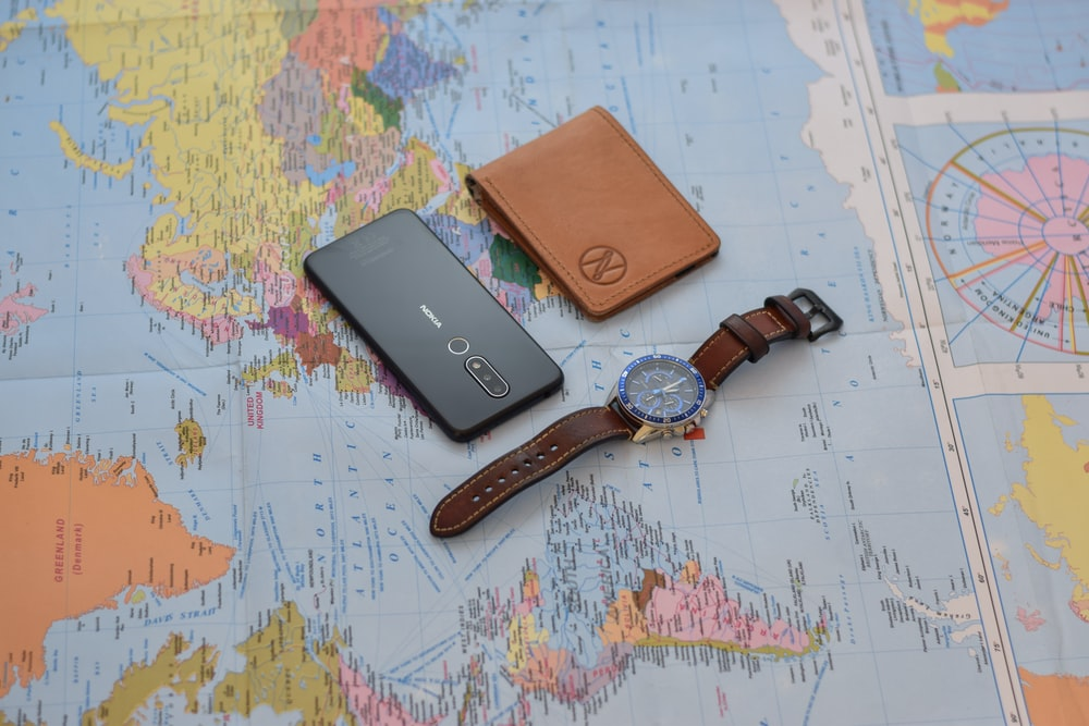 black round analog watch with brown leather strap on white and blue map