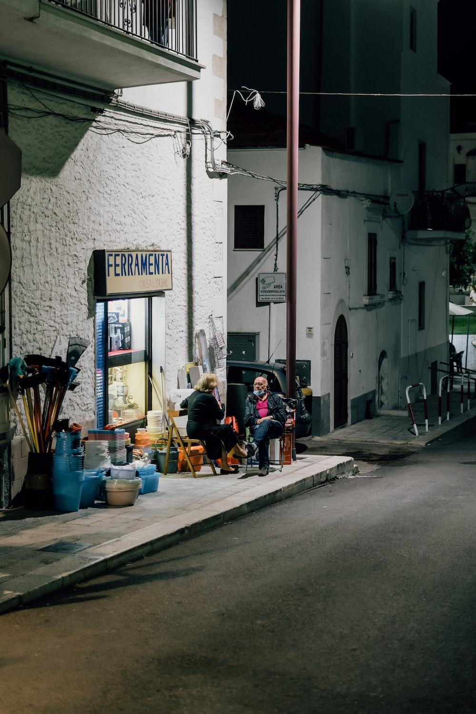 people sitting on sidewalk near building during daytime