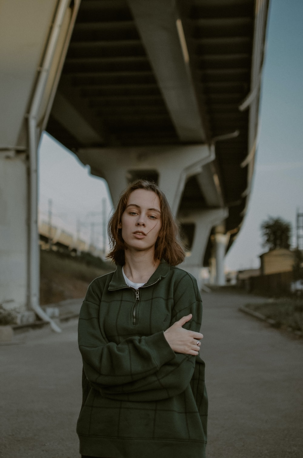 woman in green jacket standing on gray concrete road during daytime