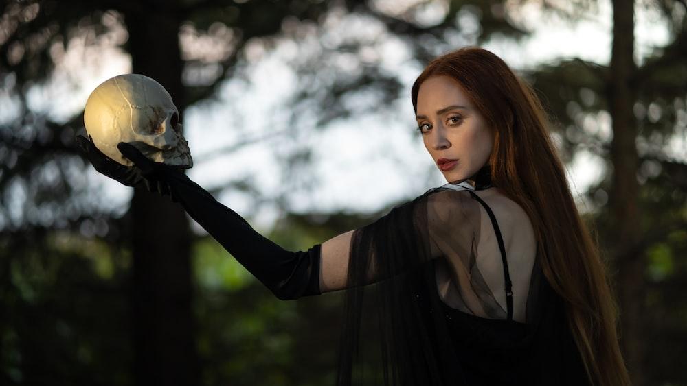 woman in black long sleeve shirt holding white bird