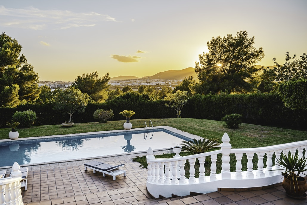 white outdoor pool near green trees during sunset
