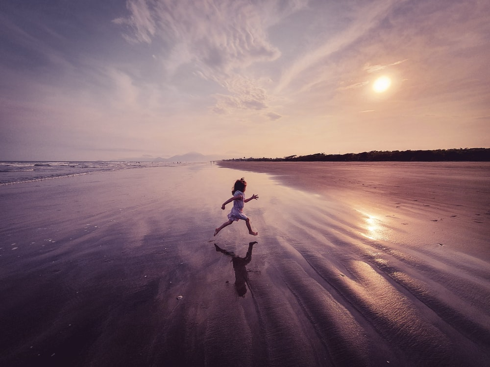 woman in white tank top and black pants running on beach during sunset