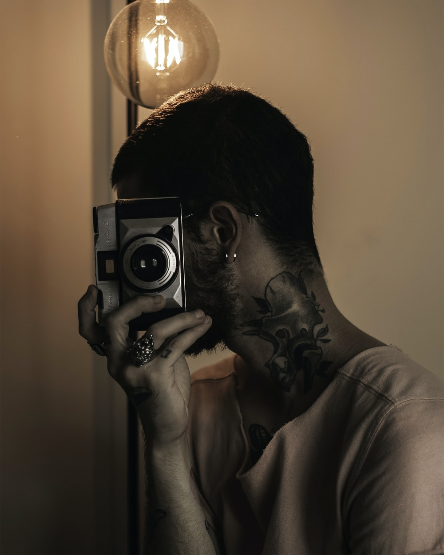 man in white shirt holding camera