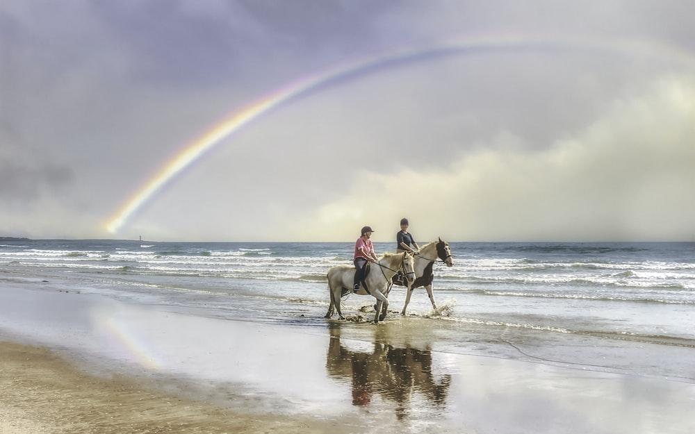 2 men riding horses on beach during daytime