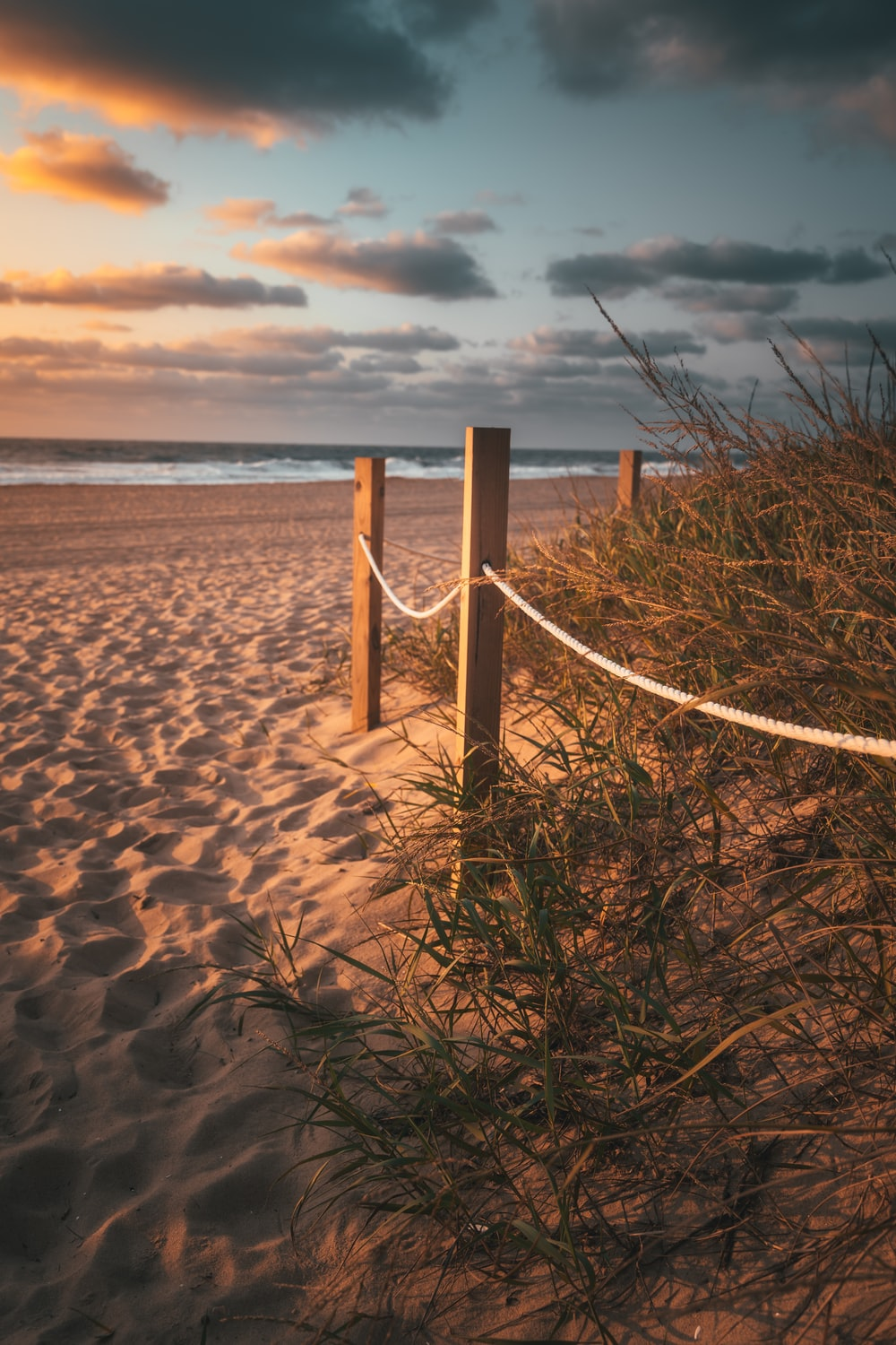 white wooden fence on brown sand near body of water during daytime