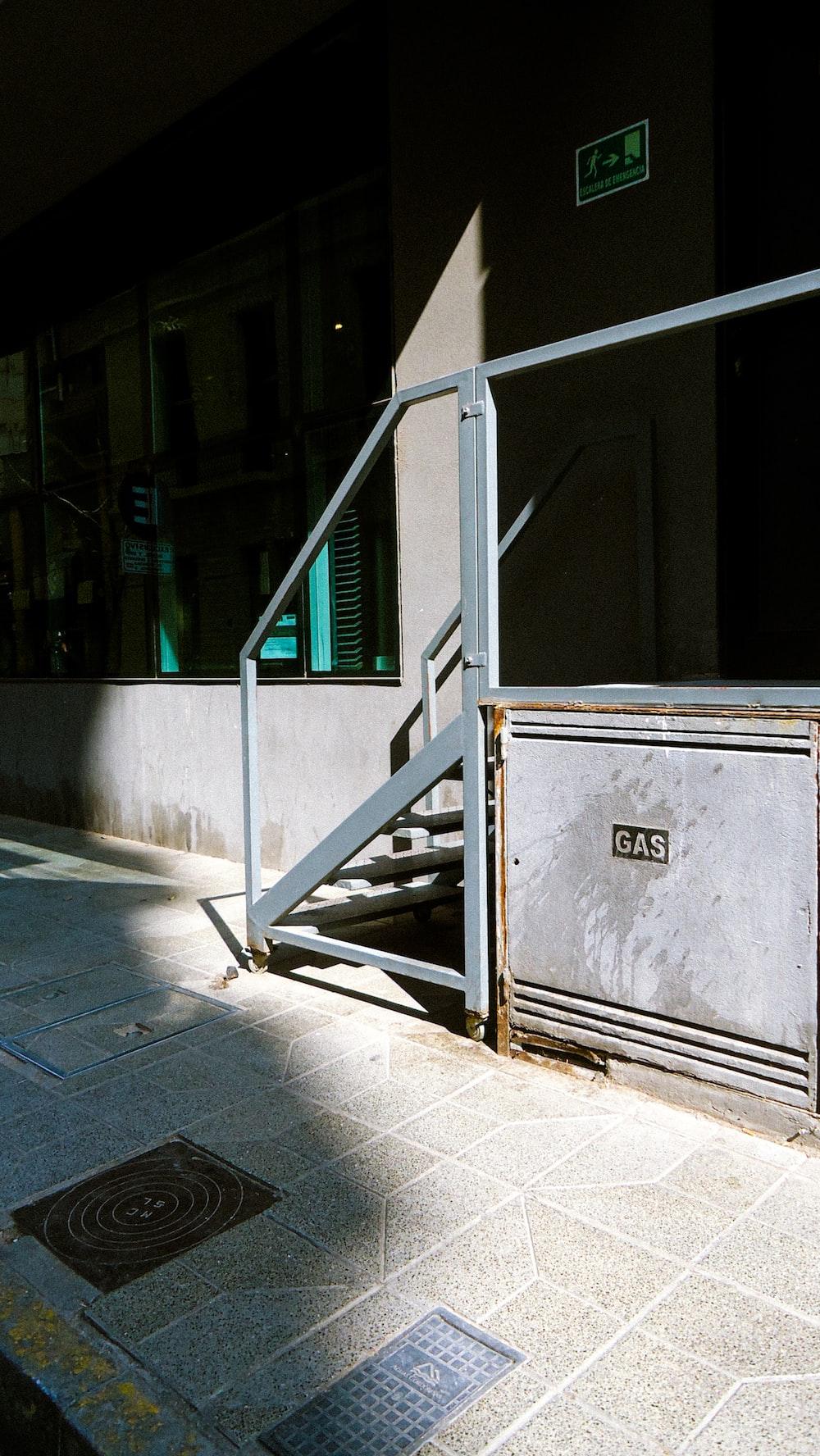 white and gray trash bin beside gray concrete building