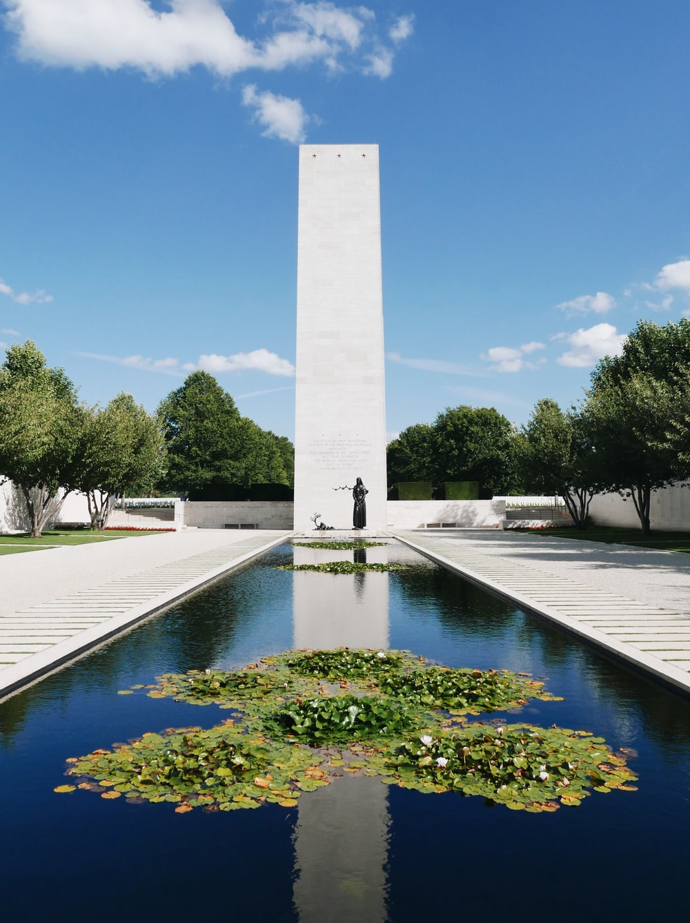 gray concrete monument near green trees under blue sky during daytime