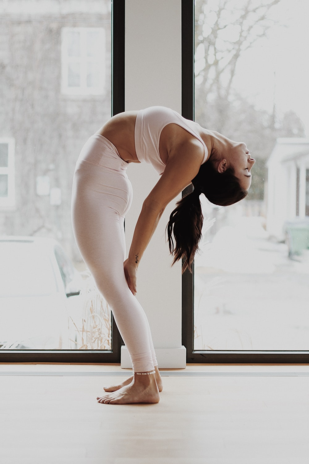 woman in white tank top and white pants bending her body by the window