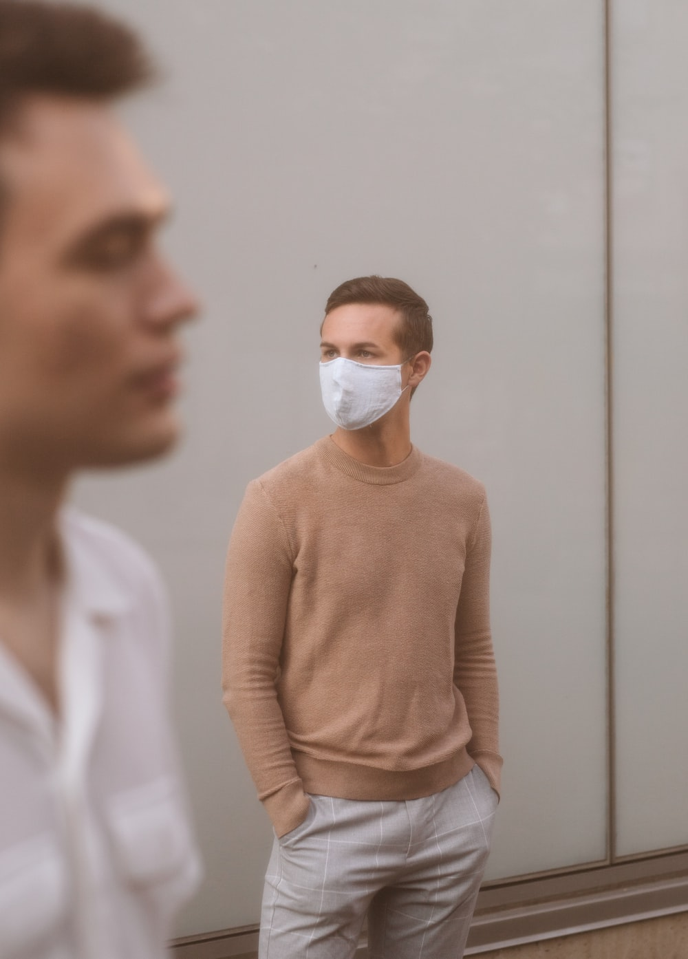 woman in brown sweater wearing white face mask