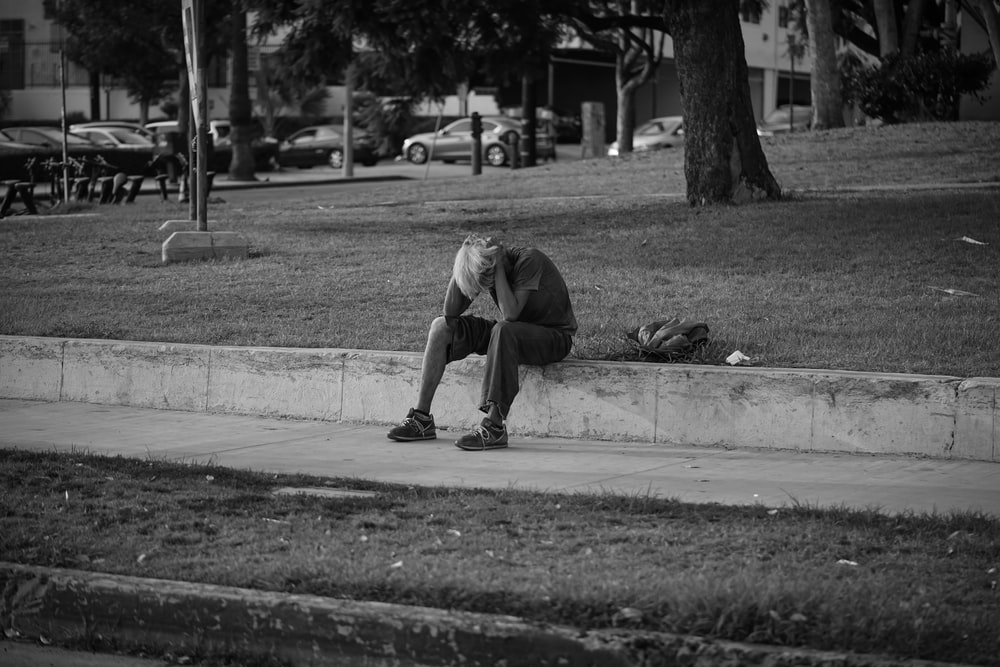 man in t-shirt and pants sitting on concrete floor in grayscale photography