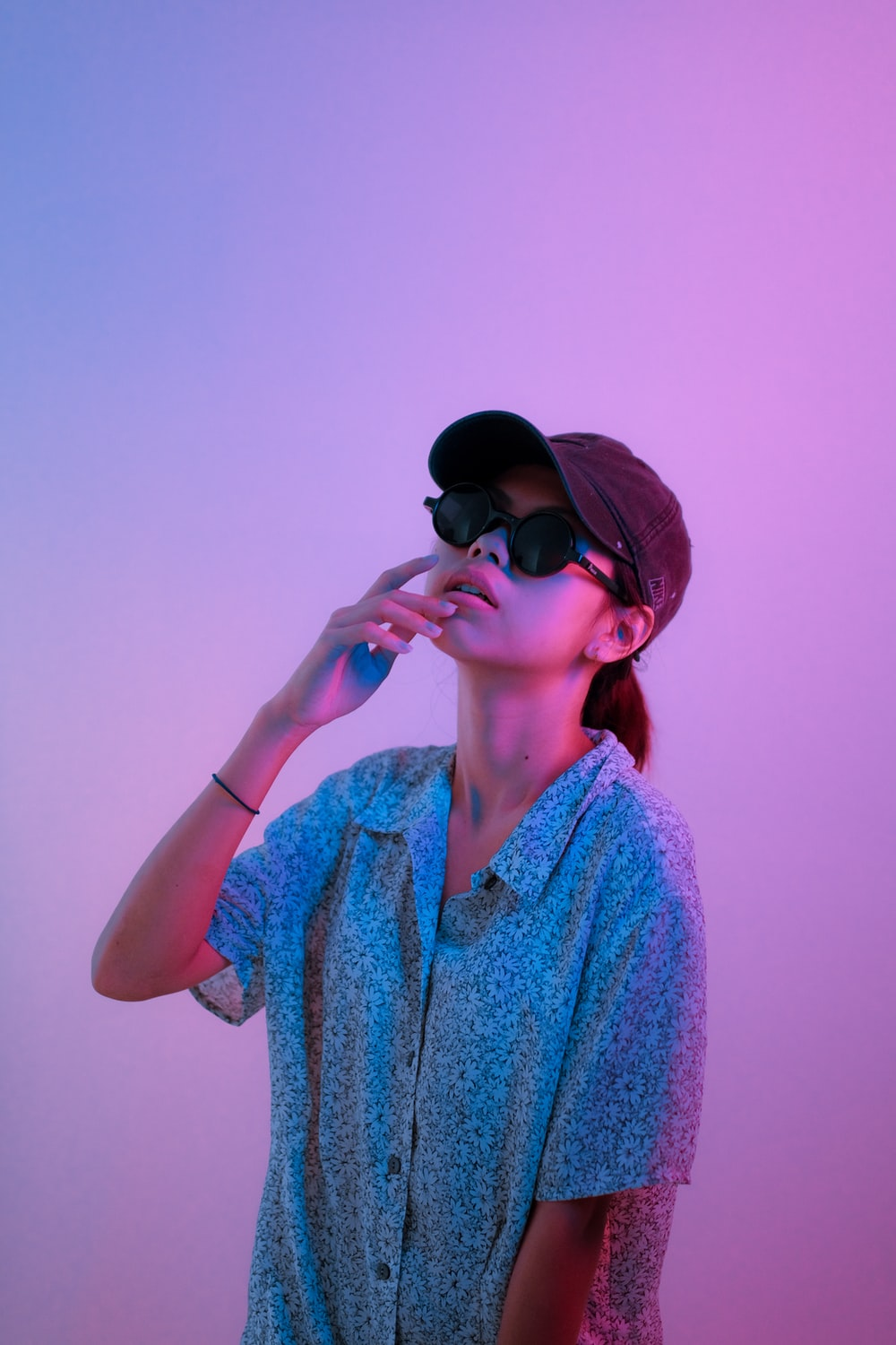 woman in blue and white floral button up shirt wearing black sunglasses