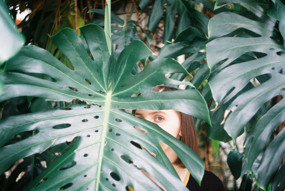 woman hiding behind green leaves