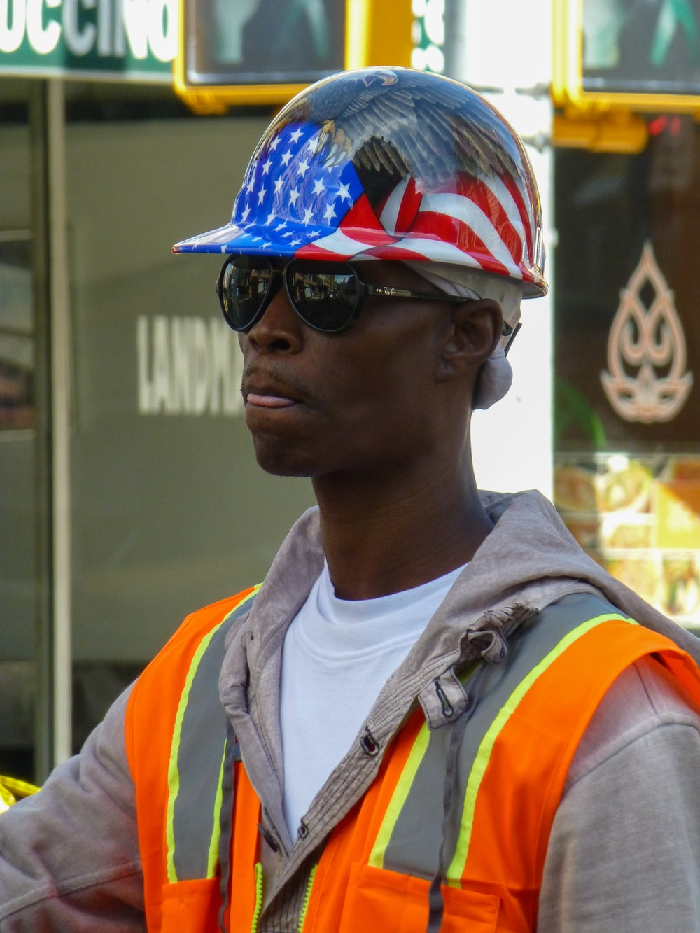 man in white and orange shirt wearing blue and white cap and black sunglasses