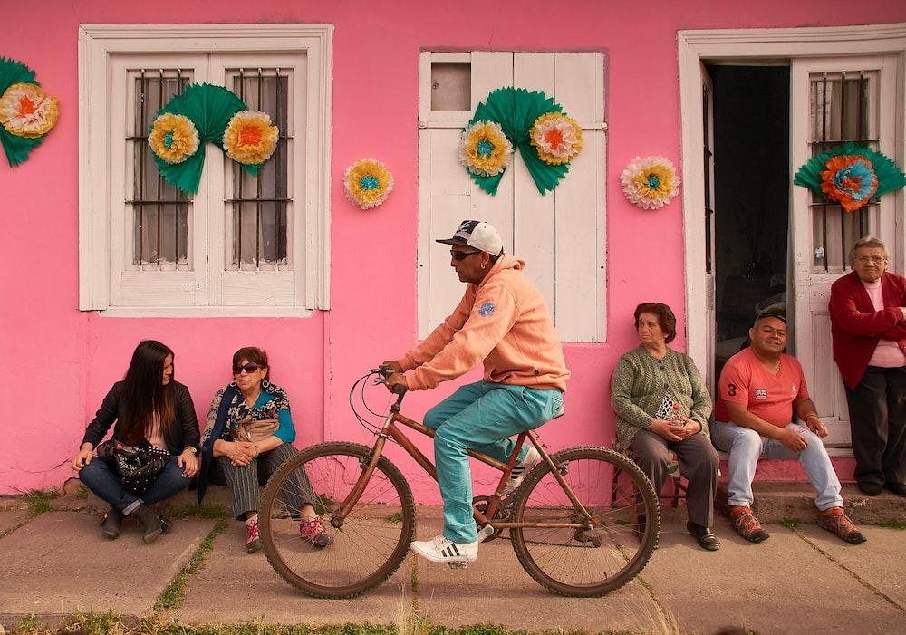 man in pink dress shirt riding on bicycle