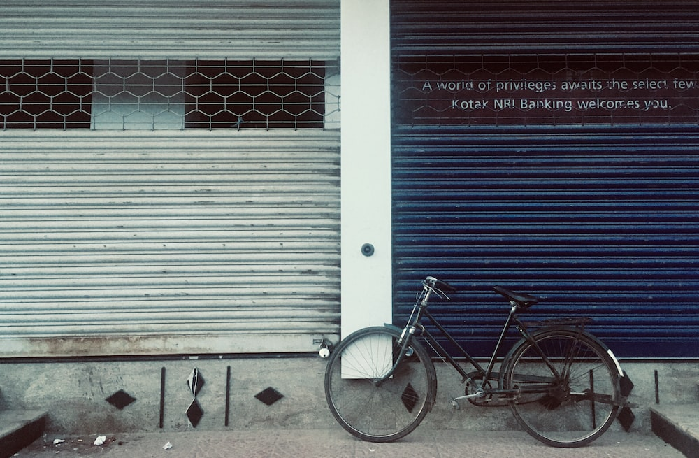 blue city bicycle parked beside white roll up door