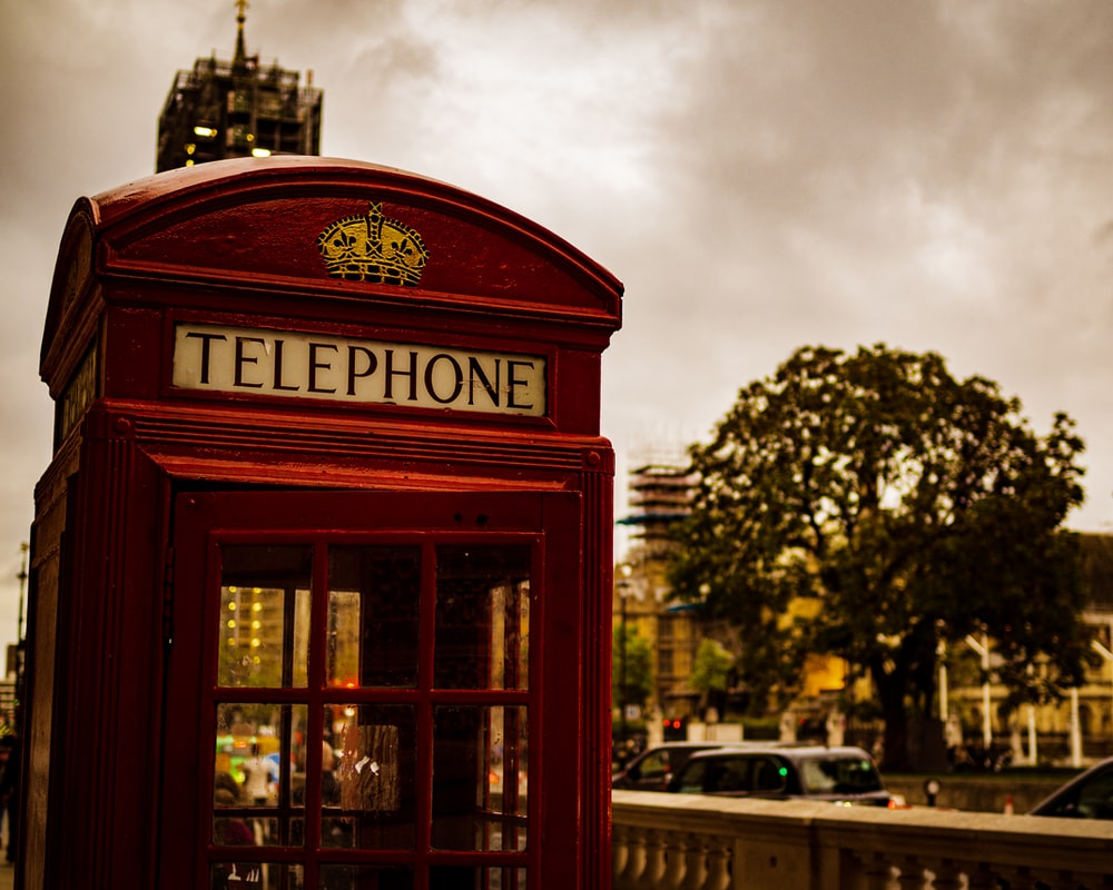 red telephone booth near road during daytime