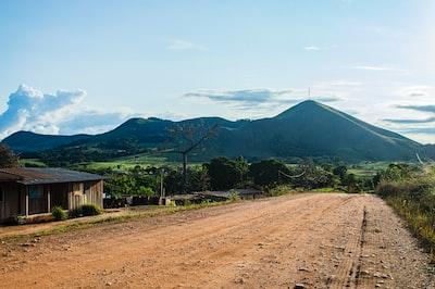 brown wooden fence near green mountain under blue sky during daytime gabon zoom background