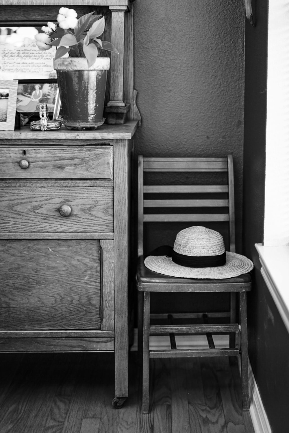 grayscale photo of hat on chair