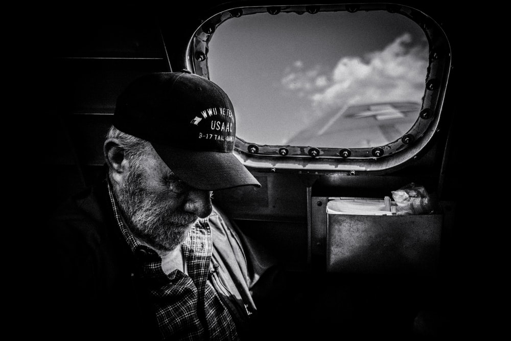 grayscale photo of man in plaid shirt and cap looking at the sky
