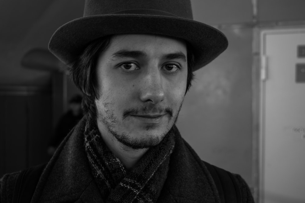 man in black hat and scarf